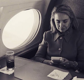 Hilary Clinton on a flight playing video game