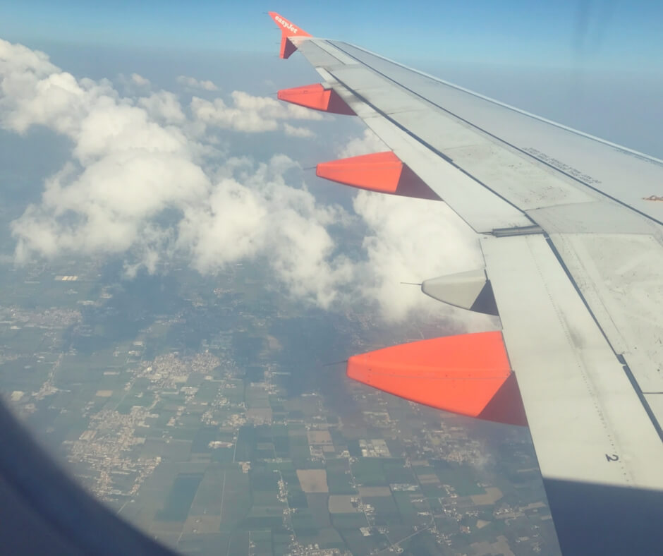 Plane wing, taken from inside the plane. Green land and clouds in the background