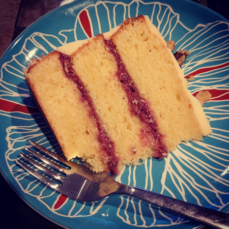 image of a slice of the cake on a plate, showing the raspberry layers between the layers of cake