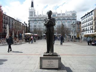 Estatua en bronce de Lorca sobre un pedestal y placa conmemorativa. Al fondo el hotel Me Madrid.