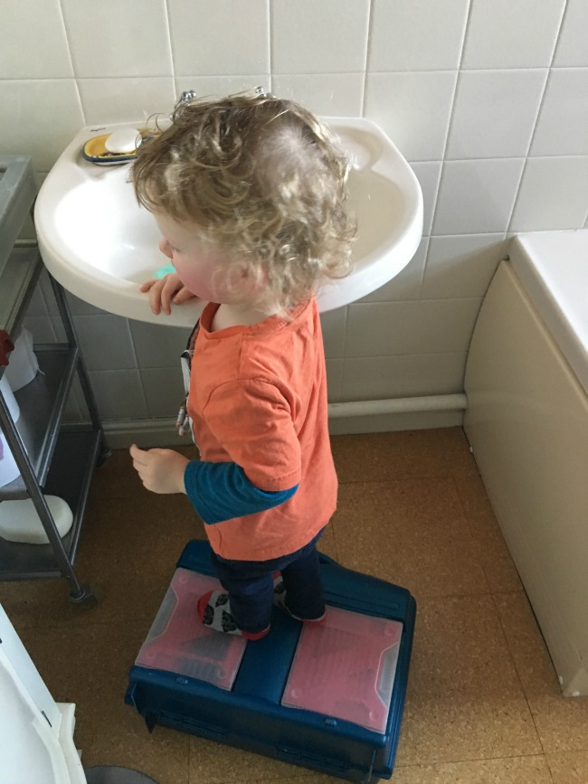 toddler stood on toolbox at bathroom sink