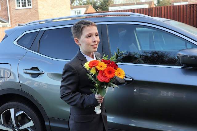 Boy standing next to a shiny car, wearing a new suit and holding a bunch of flowers.