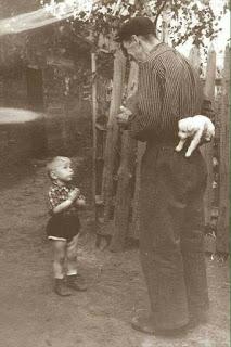 """Foto diurna antiga em preto-e-branco. Em frente a fachada de uma cabana e sobre o chão de terra, próximo a quina de uma cerca alta de madeira, um garotinho de aproximadamente três anos está em pé, com a cabeça inclinada para trás, observando o homem magro e alto em frente a ele. O garotinho está com as mãozinhas em oração, ele é loirinho e têm as perninhas gordinhas; usa uma camisa xadrez, short bufante, meias e botinhas de cano curto. O homem de perfil esquerdo, olha em direção ao garoto com a lateral do rosto em sorriso, a mão esquerda em expressão a frente do corpo e com o braço direito em """"L"""" atrás do corpo, esconde um filhotinho de Poodle que segura na mão. O homem usa uma boina, camisa listrada de mangas compridas, calça e sapatos surrados. Ao fundo, na parte interna da cerca, uma tímida árvore. A equipe de As Meninas dos Olhos Audiodescrição e Íris Cor de Mel deseja uma Feliz Páscoa!"""