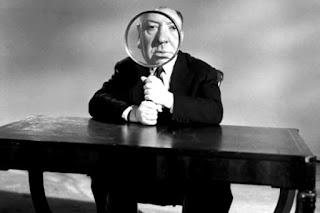 Alfred Hitchcock segurando uma lupa na frente de seu rosto