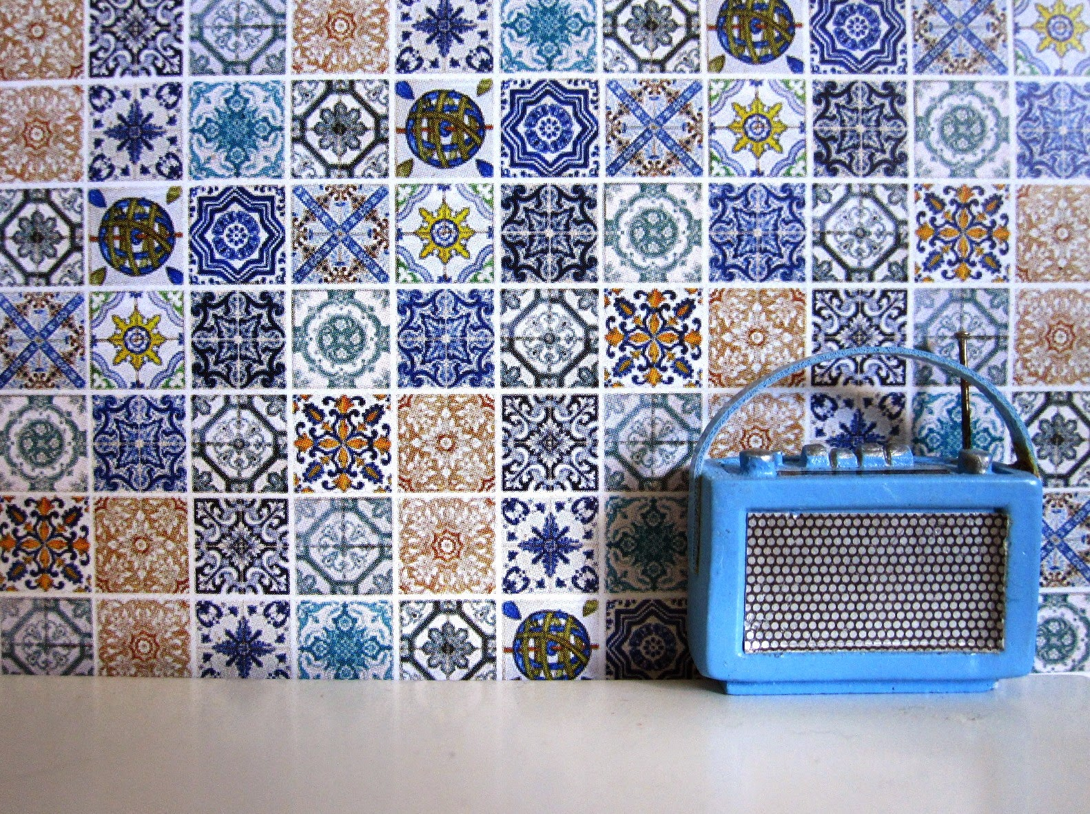 Modern dolls house miniature tiled wall in a selection of blue and white tiles. In front of it is a miniature Roberts radio in blue.