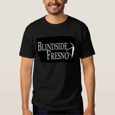 A black t shirt with the words 'Blindside Fresno' and the program logo of an eye looking to the right in white.