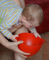 Baby wird zum Erbrechen über ein Bein gelegt Kopftieflage
