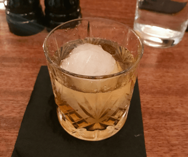 A glass of bourbon with giant ice cube