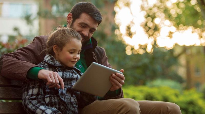 Pai ensinando a filha sobre o evangelho de Jesus Cristo sentados em um banco de praça