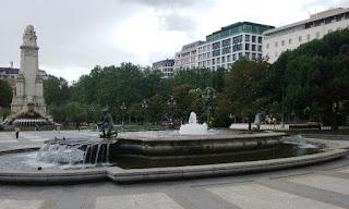 En primer término su gran fuente y más allá el monumento dedicado a Cervantes y los grandes árboles del recinto..