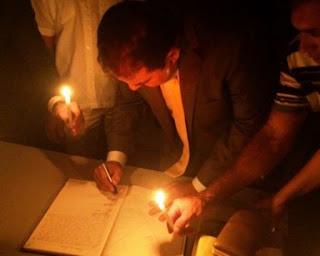 Com energia cortada, prefeito toma posse à luz de velas e usa candeeiro para entrar na prefeitura