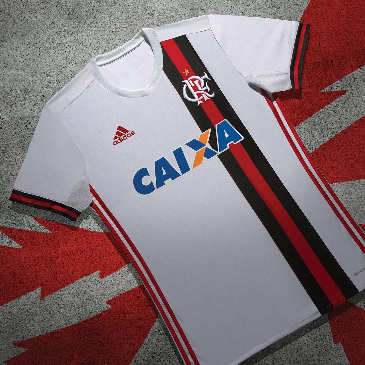 b649b5b1f6 Como de costume no modelo, a camisa é branca, mas com uma particularidade  inédita no clube até então: três listras verticais nas cores vermelha e  preta ...