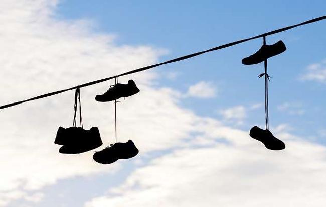 ¿Por qué hay zapatos colgando en los cables del tendido eléctrico en algunas calles?