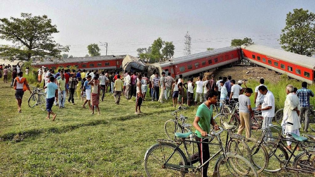 People gather around a passenger train that derailed near Chhapra town in Bihar, India, Wednesday, June 25, 2014. A passenger train derailed early Wednesday in the eastern Indian state of Bihar, killing at least four people and injuring eight others, officials said. The cause of the accident was not immediately known.