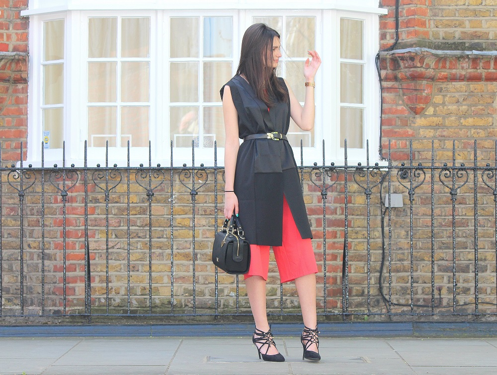peexo fashion blogger wearing culotte jumpsuit and sleeveless blazer and black belt and box bag and lace up heels in spring