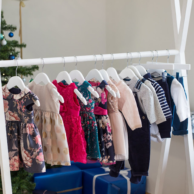 A white clothes rack with party dresses and outfits on
