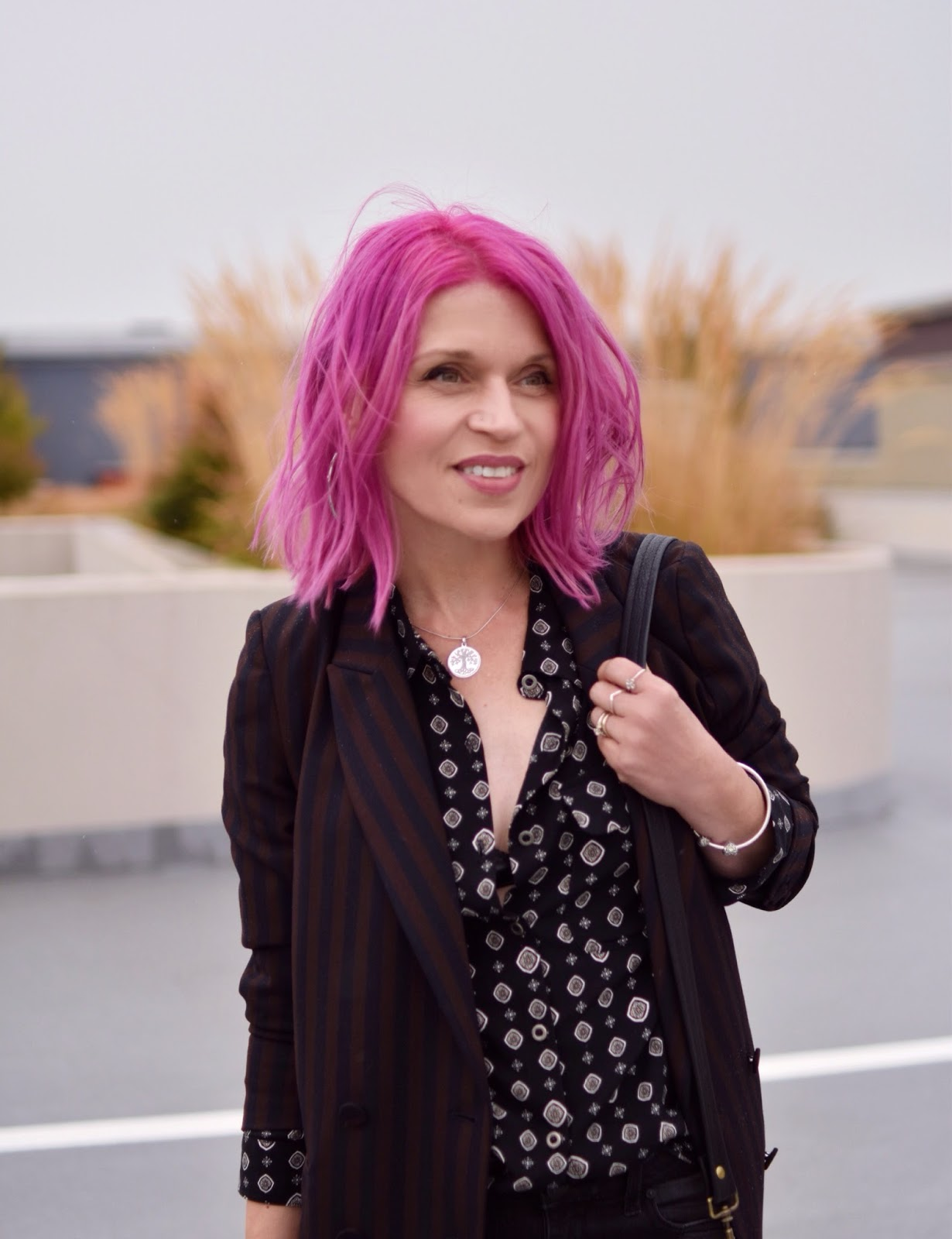 Monika Faulkner outfit inspiration - black patterned shirt, black and maroon striped suit jacket, fuchsia hair