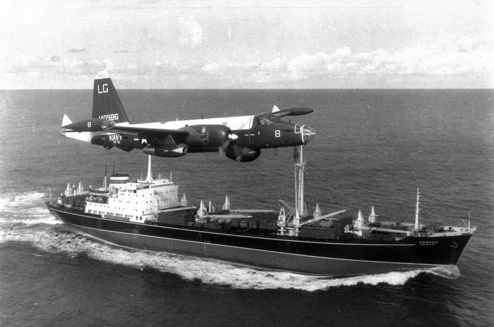 A P2V Neptune U.S. patrol plane flies over a Soviet freighter during the Cuban missile crisis in 1962.