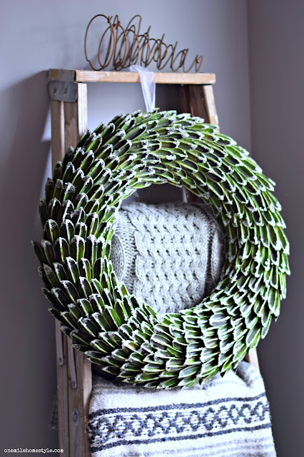 Frosted wreath winter accent on a rustic blanket ladder