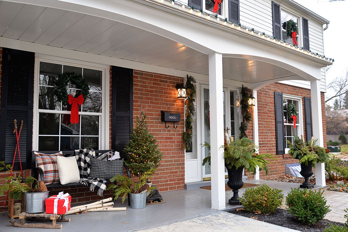 Christmas colonial house with wreaths in windows and decorated cozy Canadiana porch