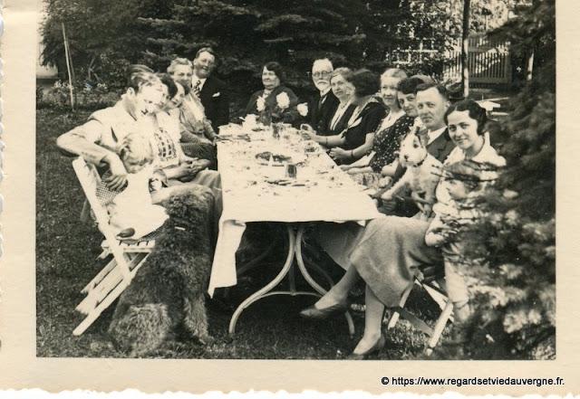 Photo noir et blanc ancienne :  toute la  famille réunie autour de la table même le chien