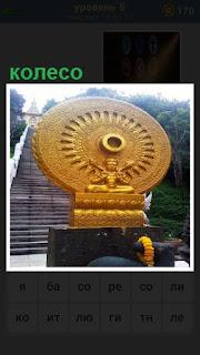 На фоне лестницы стоит желтый круг в виде колеса и внизу символ будды