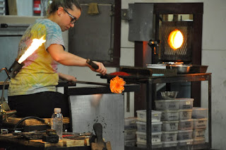 woman shaping hot glass into a flower