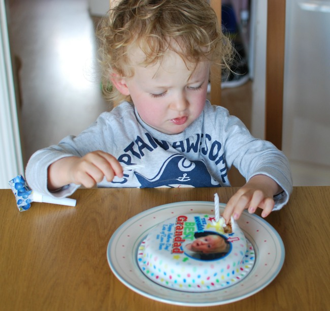 toddler pulling icing from cake