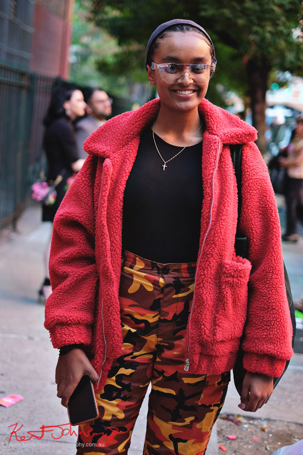 Woman in camo pants, tight black top, red fleece jacket and clear wrap glasses.  Street Fashion Sydney - New York Edition photographed by Kent Johnson