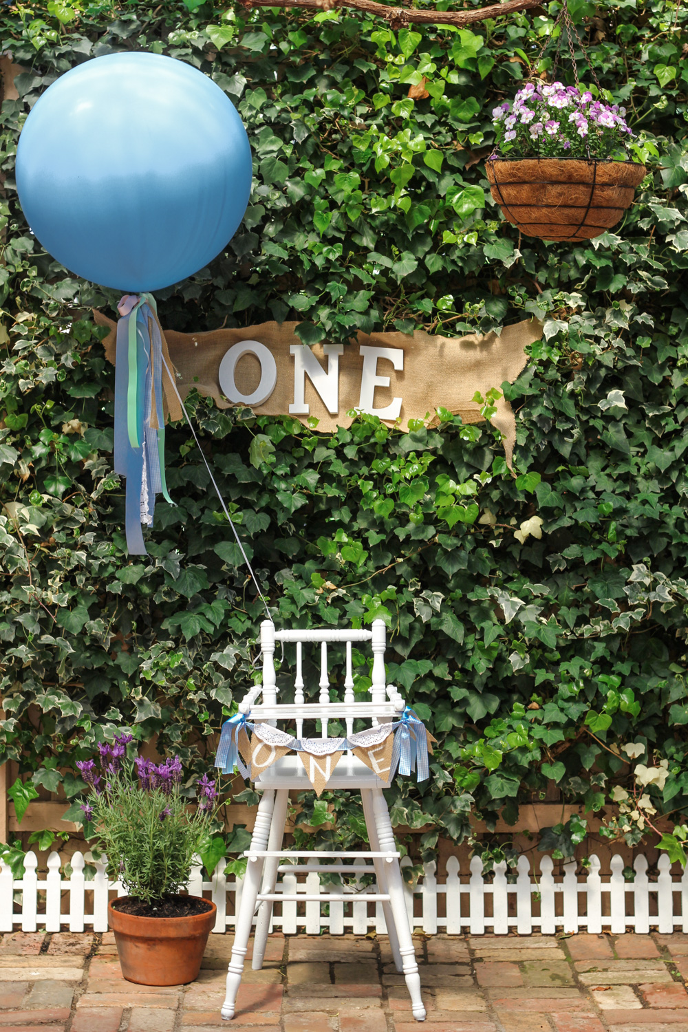 Vintage baby high chair and bunting for babys Peter Rabbit themed first birthday party