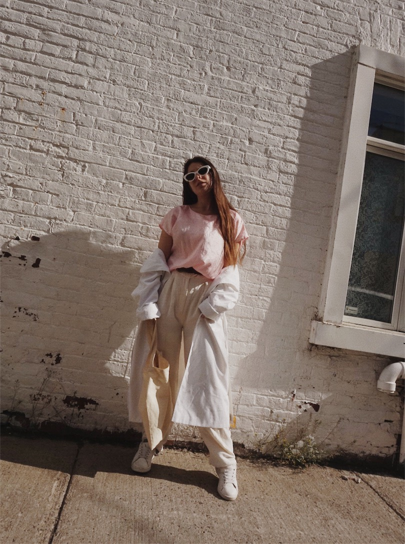 girl wearing thrifted pink shirt, sunglasses, white pants