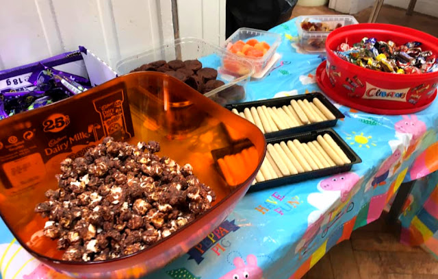 image shows a table covered with food - cakes, chocolate and sweets
