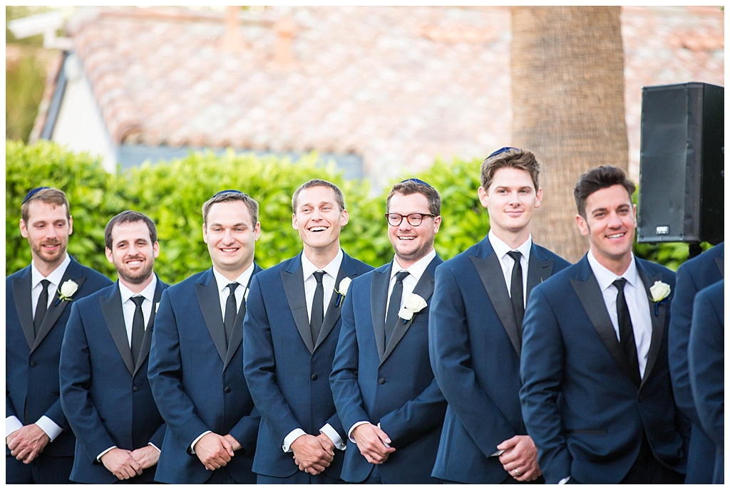 groomsmen in navy suits laughing at Omni Montelucia wedding