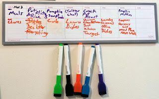 A magnetized, white board weekly calendar with purple and orange words written on it. Below it are five magnetized dry-erase markers - from left to right: green, black, orange, blue and purple.