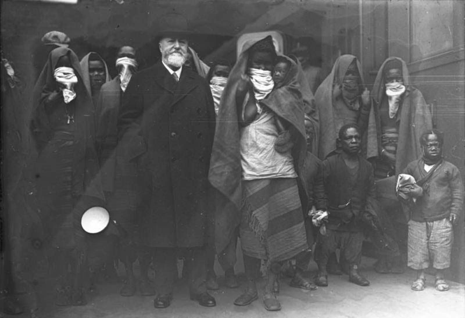 Professor Lutz Heck, director of the Berlin Zoo, arrives in Berlin, 1931. With him are members of the African Sara-Kaba tribe, who will soon be put on display. The scarves over the women's mouths are covering their lip plates.
