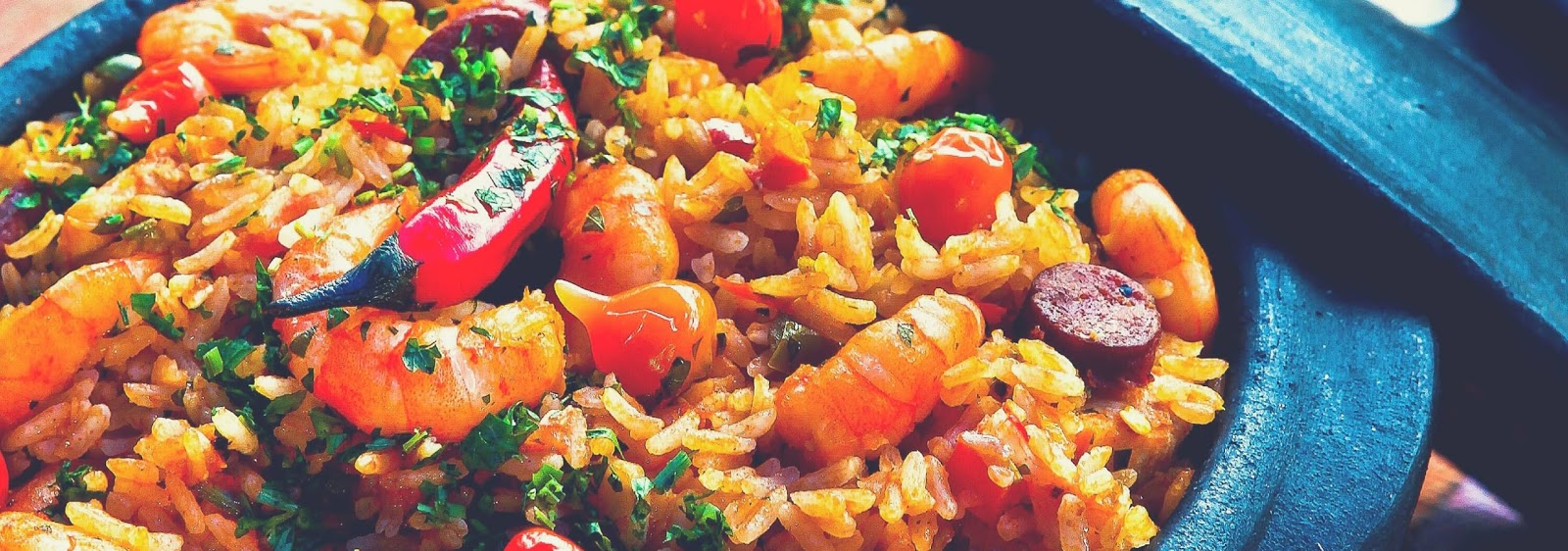 a pan filled with prawn paella. Pink prawns, red peppers, white rice.