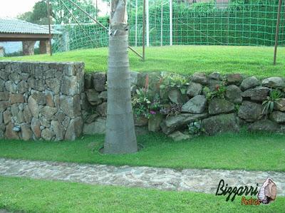 Pedra moledo na execução do paisagismo com o muro de pedra para formar o platô do campo de futebol com grama esmeralda.