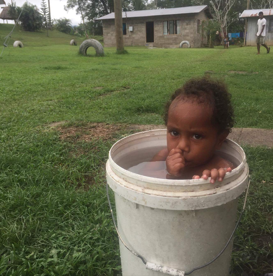 Catherine's Fijian sibling bathing in a bucket outside