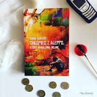 """Ksiązka """"Chłopiec z Aleppo, który namalował wojnę"""" w otoczeniu pędzla, czerwonej farby, rozwiniętego bandaża, monet i starego telefonu komórkowego."""