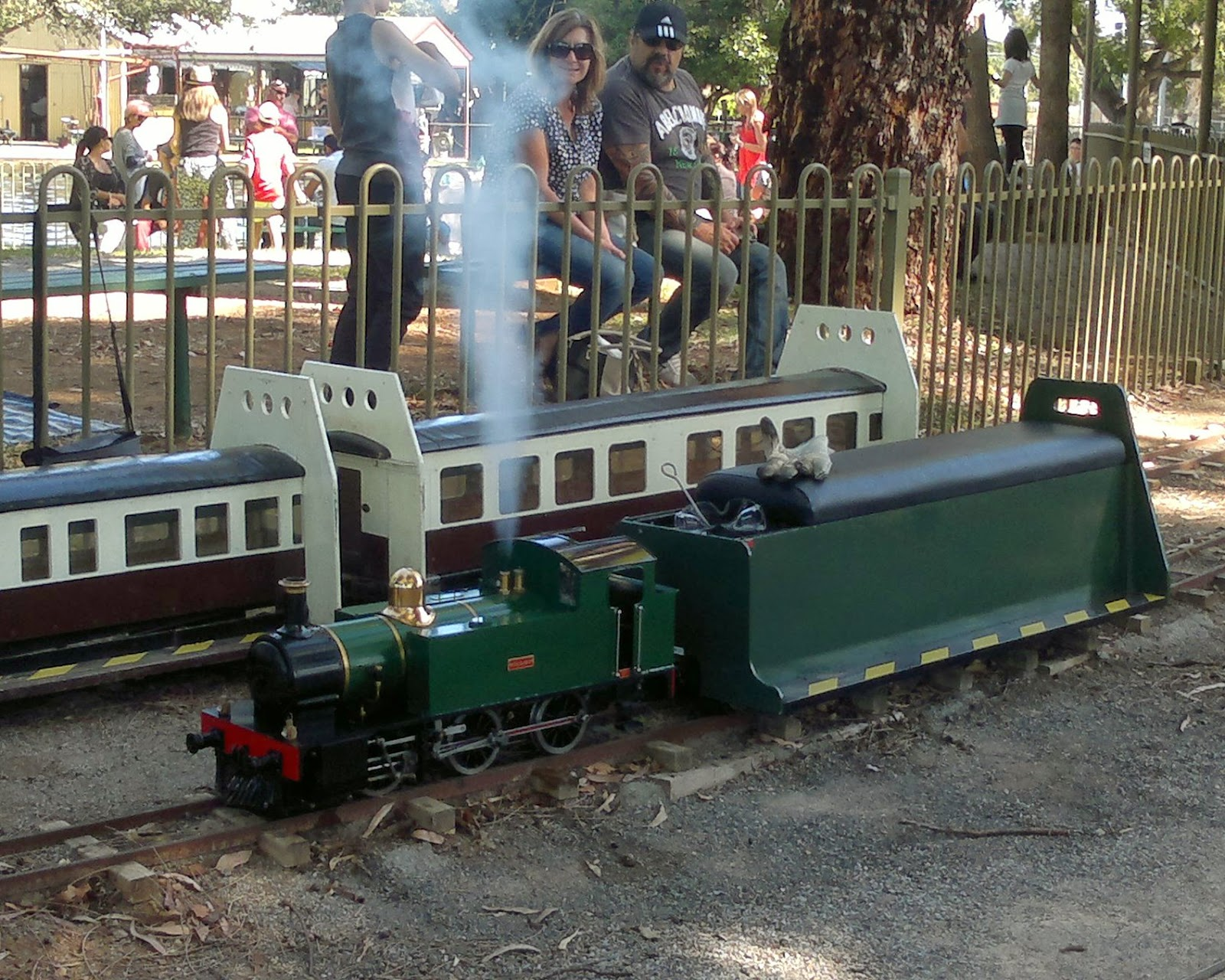 Green steam locomotive steaming up with carriage attached. In the background are two carriages for a larger locomotive.