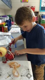 Young boy using an apple peeler