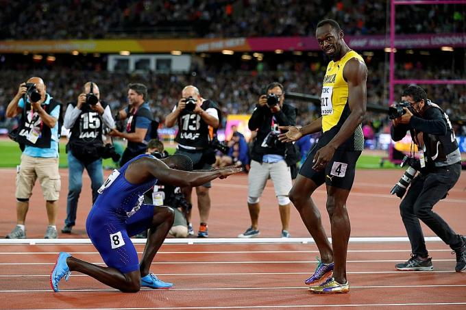 World champion Justin Gatlin (on his knees) paying homage to Usain Bolt after stunning the retiring Jamaican to win the 100m final at the World Championships in London yesterday morning.
