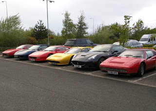Six Ferraris, all in a row. Three red, two black, one yellow. South Queensferry, Scotland