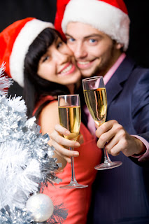 Photo of a couple in Santa hats toasting in a New Year