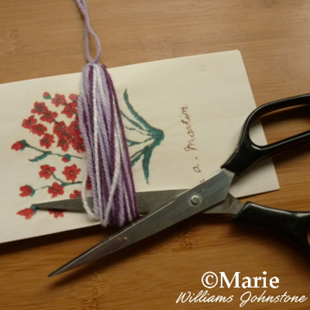 Using scissors to cut the yarn strands on the bottom of the tassel