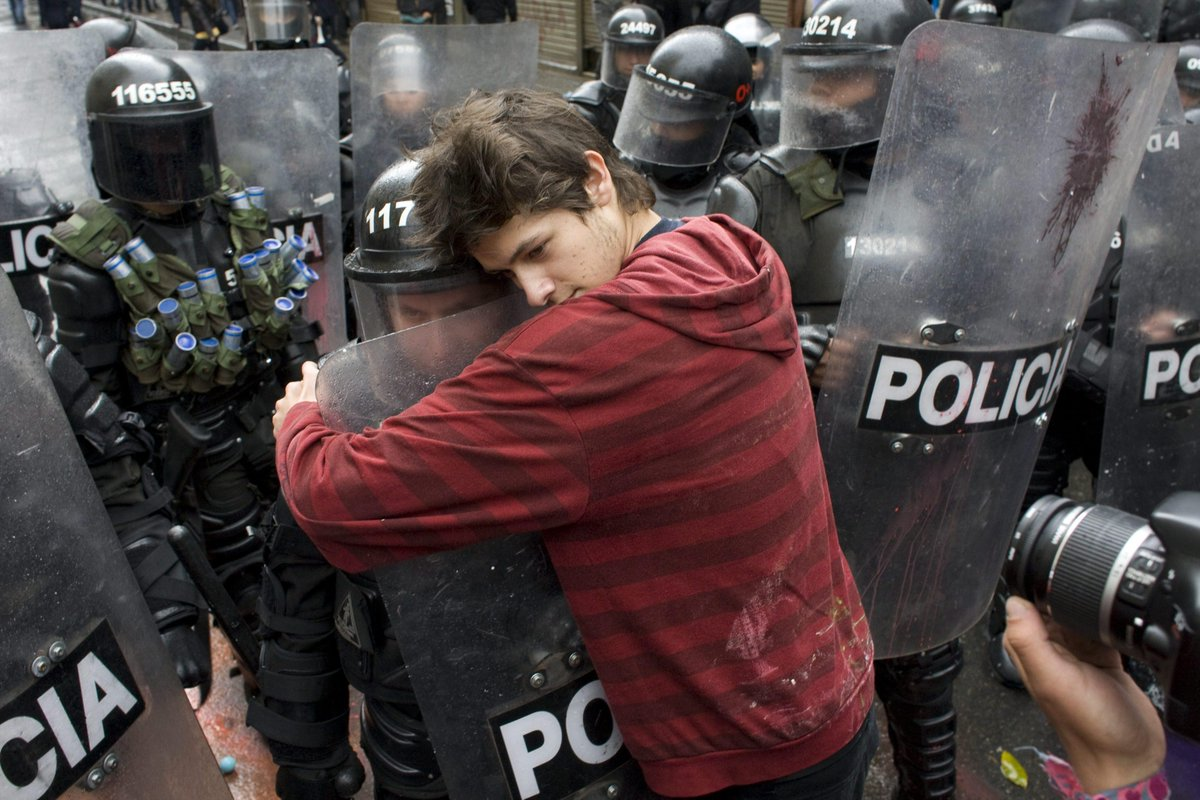 Bogota, Colombia – A demonstrator embraces a riot police officer during a student protest against government plans to reform higher education.