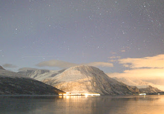 a starry sky above mountains and a fjord