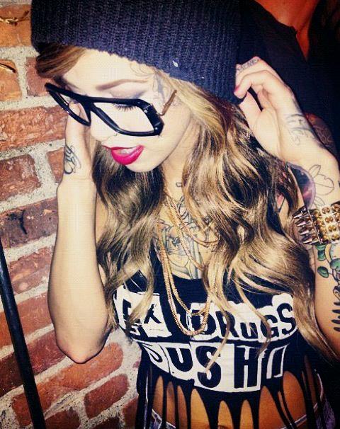 Chica latina saliendo de discoteca, lleva tatuajes modernos en los brazos