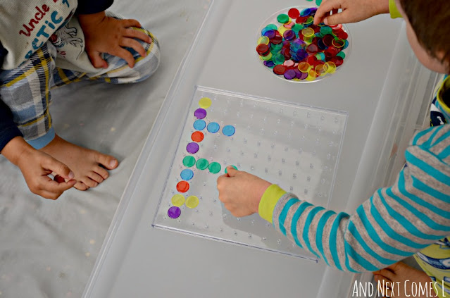 Kids making colorful math patterns on a clear geoboard