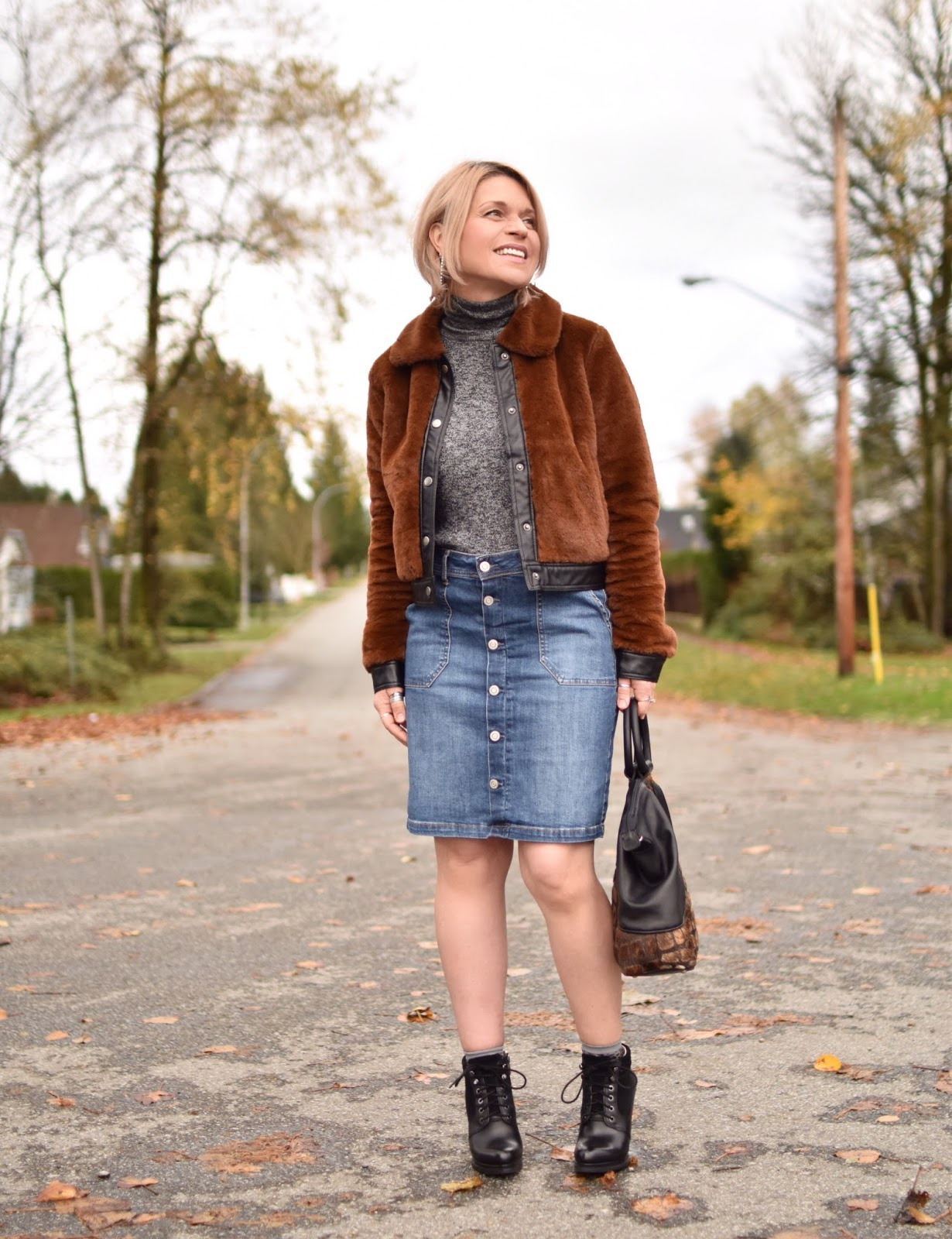 Monika Faulkner outfit inspiration - styling a faux-fur bomber jacket with a turtleneck sweater, button-front denim skirt, and lace-up booties